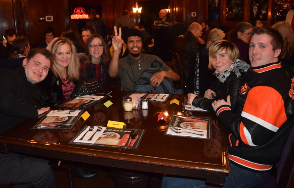 A group of people sitting around a table in a dark restaurant. One of the people at the center is holding up the Peace sign with his fingers.