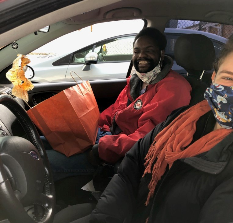 Two people sitting in car smiling after picking up new iPads