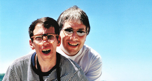 Photo from Oregonian of two people, one of whom has short dark hair and is wearing glasses and a striped t-shirt. The other stands behind him and has on mirrored sunglasses and a white t-shirt. Both have their mouths open against a blue sky background.