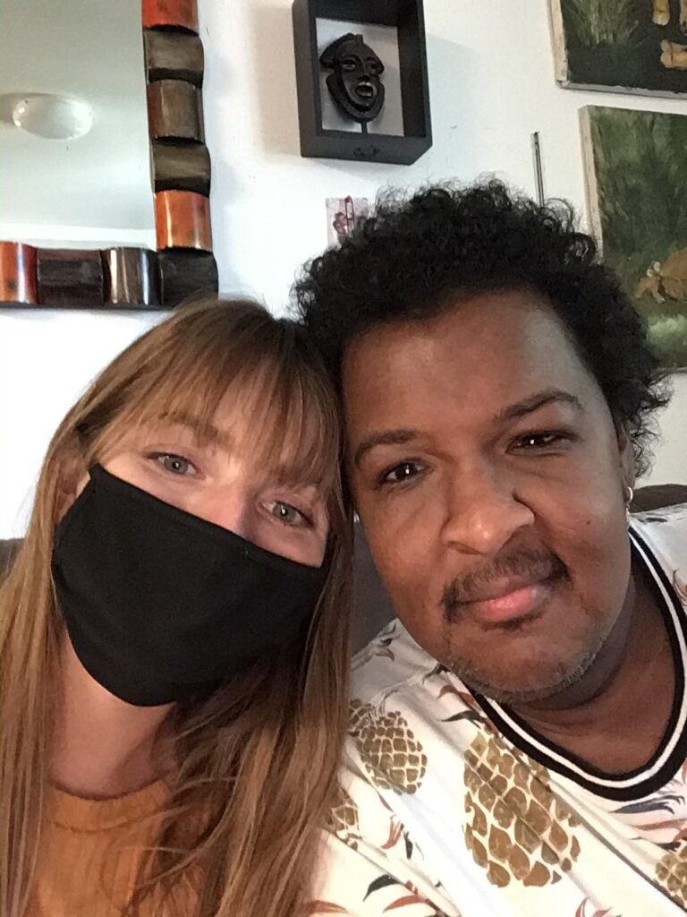 Two people close up. One is wearing a mask with her head resting against the other person's head. Then other person has a mustache and is wearing a white shirt with large prints of pineapples on it.